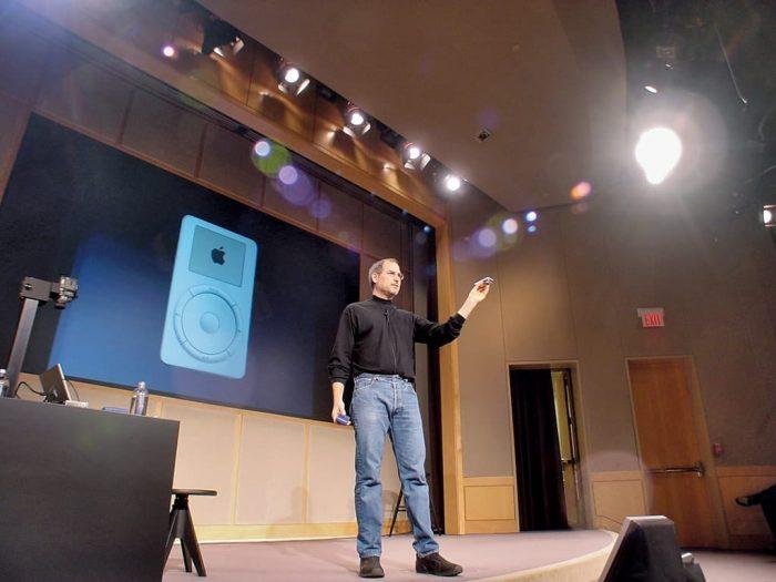 Ze względu napoczątkowe ograniczone oczekiwania firmy wobec produktu, prezentacja iPoda 23 października 2001 roku niebyła wielkim wydarzeniem. Nazdjęciu Steve demonstruje urządzenie prasie ipracownikom wauli Apple'a wCupertino. Dzięki uprzejmości Brenta Schlendera (zdjęcie pochodzi zksiążki Droga Steve'a Jobsa)