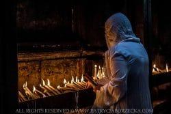 Chrześcijanka zapalająca świece wBazylice Grobu Świętego. Jerozolima, Izrael, lipiec 2014.